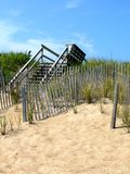 Boardwalk to the Beach. A well-trod boardwalk descends down to a weathered dune fence and grassy sand dunes at the Nags Head Beaches in the Outer Banks of North Royalty Free Stock Images