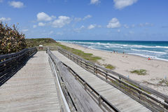 Boardwalk to the beach. Old wooden boardwalk provides beach access to the handicapped, as well as protecting the sand dune Stock Photography