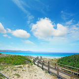 Boardwalk to the beach under clouds Stock Image