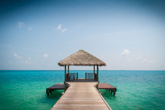 Boardwalk to the ocean. Wooden jetty leads the eye toward the ocean in the Maldives Stock Photos