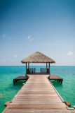 Boardwalk to the ocean. Wooden jetty leads the eye toward the ocean in the Maldives Royalty Free Stock Photos