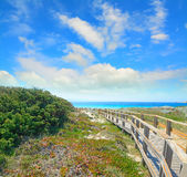 Boardwalk under a cloudy sky in Capo Testa Stock Image