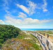Boardwalk under a cloudy sky in Capo Testa Stock Image