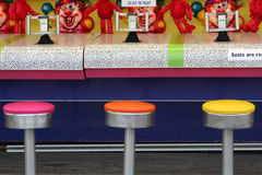 Boardwalk Water Game. Colorful seats at a shooting water game booth on a boardwalk Royalty Free Stock Photos