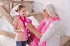 Boas de plume de port avec plaisir gentils de grand-mère et de petite-fille Photos stock