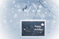 Boas festas escrito na placa de giz preta que pendura de uma árvore no fundo azul, nevado Ornamento da árvore de Natal fotos de stock royalty free