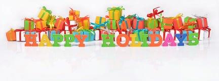Boas festas texto colorido no fundo dos presentes Fotos de Stock Royalty Free