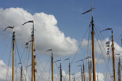 Boat 11. Masts of sailing boats with flags against a cloudy sky Stock Photos