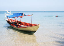 Boat. A boat  at an iddylic beach in Cambodia. In the background a buddhist monk is swimming Royalty Free Stock Images