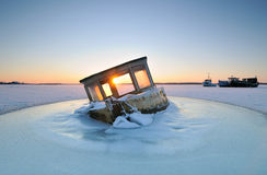 Boat. Trapped in the ice at sunset Royalty Free Stock Photography
