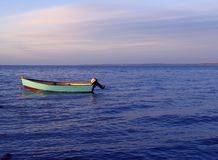 Boat. Dinghy in the sunset on a very blue sea royalty free stock photo