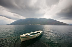 A boat. Tied with a rope. Storm beginning, dark clouds above, strong wind, a distant misty island on the background Stock Image