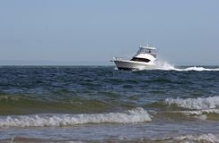 Boat. Cruiser moving close to shore Stock Photography
