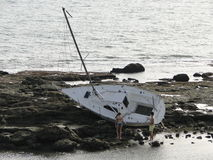 Boat accident. Sailboat that has had an accident running aground on the beach on some rocks Royalty Free Stock Image