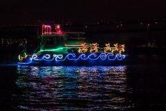 Boat Adorned with Christmas Holiday Lights, Santa Claus Sleigh and Reindeer and Reflection in the Water. Boat in the river Adorned with Christmas Holiday Lights royalty free stock image