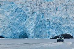 Boat against glacier at Prince William Sound, USA. Tour boat against melting glacier at Prince William Sound, Alaska, USA Stock Images