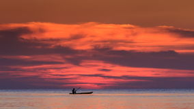 Boat along Horizon against Red Clouds in Dark Sky after Sunset. Silhouette of boat floating on paddles along skyline against red clouds in dark sky after sunset stock video