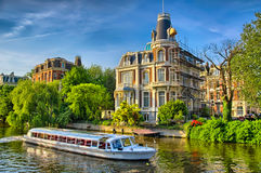 Boat on Amstel river near beautiful houses in Amsterdam, Holland Royalty Free Stock Images