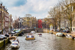 Boat at Amsterdam canals in Holland, traditional houses, street view Royalty Free Stock Images