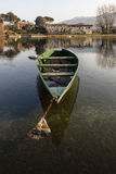 Boat at anchor. A green long boat anchored near the banks of a river royalty free stock photography