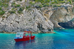 Blue water background. Boat anchored in bay - Ionian Sea, Zakynthos Island, landmark attraction in Greece. Seascape Stock Photo