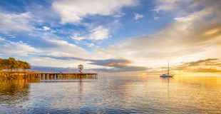 Sunrise lightens sky in Port Angeles, Washintong. A boat anchored on the calm waters of the Puget Sound as the early morning sun rays warm the cloud ridden sky stock images