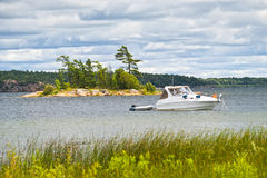 Boat anchored on lake. Motorboat anchored with dinghy on lake in Georgian Bay, Ontario, Canada Royalty Free Stock Images