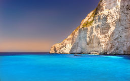 Boat anchored on Navagio beach (also known as shipwreck beach), Zakynthos island, Greece. Side view of Navagio beach in Greece with cruiser anchoring next to Stock Image