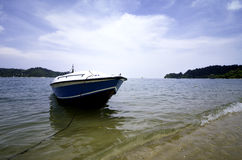 Boat anchored near the beach, cloudy sky and soft wave hitting the beach. Royalty Free Stock Photography