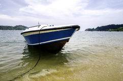 Boat anchored near the beach, cloudy sky and soft wave hitting the shore background. Royalty Free Stock Photo