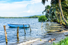 Boat anchored off tropical beach Royalty Free Stock Photo