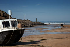 A boat anchored on the sand by the sea Royalty Free Stock Photography
