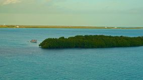 A boat anchored by a small island at sunrise stock footage