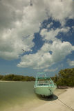 Boat anchored on white sand beach. Boat anchored on a white sand beach on the Caribbean coast, in a mangrove area under cloudy sky Stock Photo