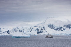 A boat in antarctic landscape. Antartica - circa December 2008 - antarctic tourism - people travel in old research boat to admire the antarctic landscape Stock Photo