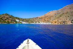 Greek village of Loutro, Chania, Crete, Greece. Boat approaches the greek village of Loutro, Chania, Crete, Greece Stock Photo