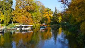 Boat approaching jetty in autumn lake stock video footage