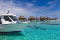 Boat arrives at tropical over water bungalow resort paradise in Tahiti. Overwater bungalows sit on top of turquoise tropical waters in beautiful island setting stock photography
