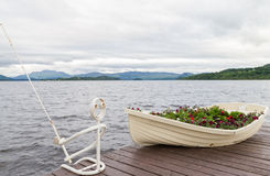 Boat as flower pot and iron fisherman on pier on lake Royalty Free Stock Image
