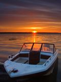 Boat Ashore. A fishing boat on the shores of a lake at sunrise royalty free stock image