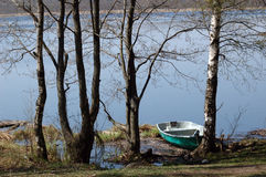 Boat ashore lake. Rowboat stranded ashore at a lake in Russia Royalty Free Stock Photo