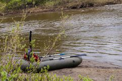 Boat ashore. The river bank of the small small river with a rapid current. The inflatable boat with oars ashore Stock Photo