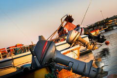 Boat with attached outboard motor in harbor. Taken at the harbor of Boderne, on the island of Bornholm, Denmark. August 5, 2016 stock photo
