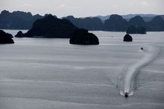 Boat Bai Tu Long Bay, Vietnam. Boat leaves wake as it crosses Bai Tu Long Bay, Vietnam, with stunning karst landscape Stock Photos