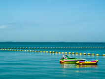 Boat and banana boat near barrier Royalty Free Stock Image