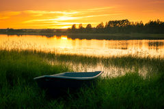 Boat on bank of river at sunset in grass Stock Photos