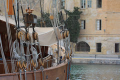 Boat and bar Malta. A historic boat moored in the harbour of Vittoriosa, with a bar in the background Royalty Free Stock Photography