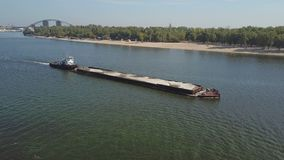 Boat with a barge on the river Dnieper. Towing boat pulls a large barge with sand on the Dnieper River in Kiev Ukraine. Aerial survey stock footage