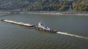 Boat with a barge on the river Dnieper. Towing boat pulls a large barge with sand on the Dnieper River in Kiev Ukraine. Aerial survey stock video footage
