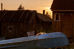 Boat and barns in sunset. With old blue boat Stock Images